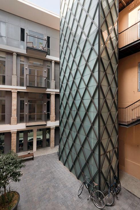החצר הפנימית. מימין: מגדל המעלית. ובקומת הקרקע החנויות שקירות הבלוקים שלהן הוחלפו בזגויות  (צילום: ליאור גרונדמן)