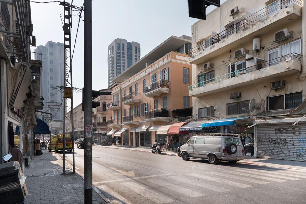 """חזיתות הבניין צבועות בגוון ורוד קשה להגדרה, שאי אפשר להתעלם ממנו ברחוב המוזנח. """"אני אוהב גוונים שלא יודעים מה השם שלהם"""", אומר האדריכל, """"גווני הביניים הרבה יותר עשירים"""". מעל שני הבניינים המחוברים נוספה קומה חדשה בנסיגה מקו החזית, כך שבקושי ניתן לראות אותה מהרחוב   (צילום: ליאור גרונדמן)"""