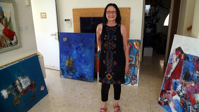 נתנה ליד לספר את סיפורה. שיש על גבי הציורים בביתה (צילום: יריב כץ) (צילום: יריב כץ)