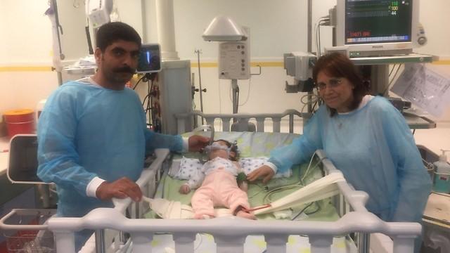 """פרופ' פתאל ואבי התינוקת ליד מיטתה. """"מצבה קריטי"""" ( ) ( )"""