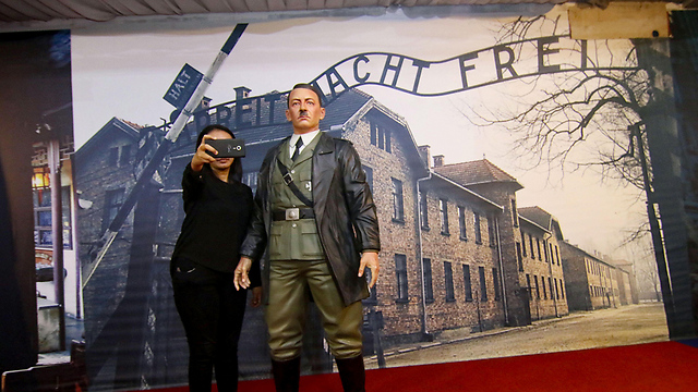 Visitor taking a selfie with the sculpture of Hitler (Photo: AFP)