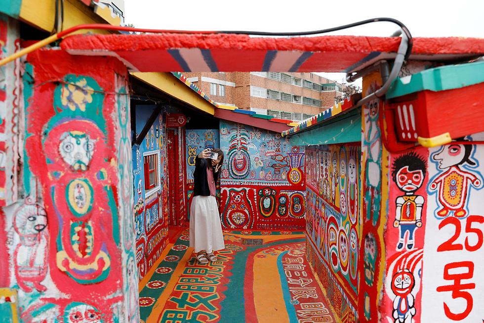 """תיירת מצטלמת ב""""כפר קשת בענן"""" - אמנות רחוב שנוצרה על ידי חייל לשעבר בעיר טאיג'ונג, טייוואן, ונחשבת לאטרקציה תיירותית (צילום: רויטרס) (צילום: רויטרס)"""