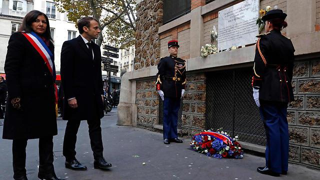 נשיא צרפת עמנואל מקרון וראש העיר פריז אן אידלגו בפינה לזכר הנרצחים בפריז (צילום: AFP)