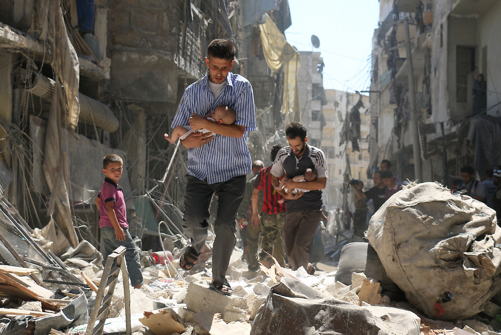 חאלב שבסוריה הפכה לשדה הקרב העיקרי במלחמה בין הכוחות הנאמנים לנשיא בשאר אסד ובין המורדים שניסו להפילו. בצילום, גברים ותינוקות בידיהם, מפלסים את דרכם בין הריסות שכונת סאליהין (צילום: Walid Mashhadi, Agence France-Presse) (צילום: Walid Mashhadi, Agence France-Presse)