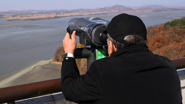 תייר בדרום קוריאה צופה במשקפת על צפון קוריאה בגבול בין המדינות (צילום: AFP) (צילום: AFP)