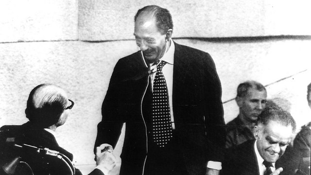 Sadat (center) shakes Begin's hand at the Knesset. Then-Knesset Speaker Yitzhak Shamir can be seen on the right  (Photo: AP)