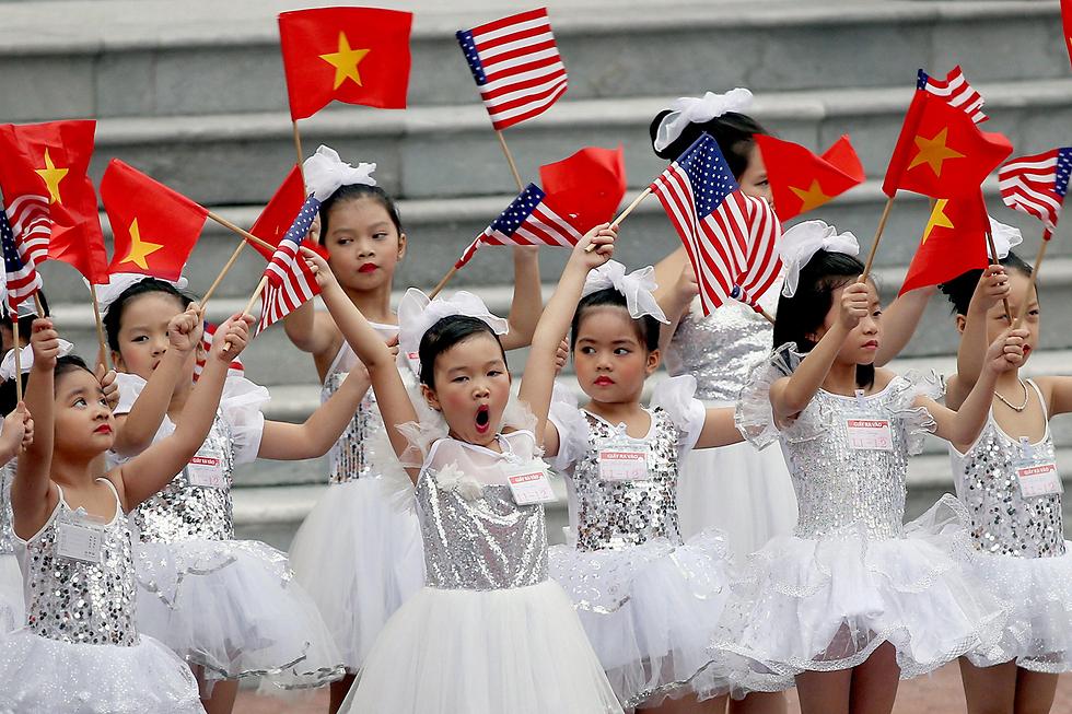 """ילדות מנופפות בדגלי ארה""""ב ווייטנאם במהלך טקס קבלת הפנים לדונלד טראמפ בארמון הנשיאותי בהאנוי (צילום: EPA) (צילום: EPA)"""