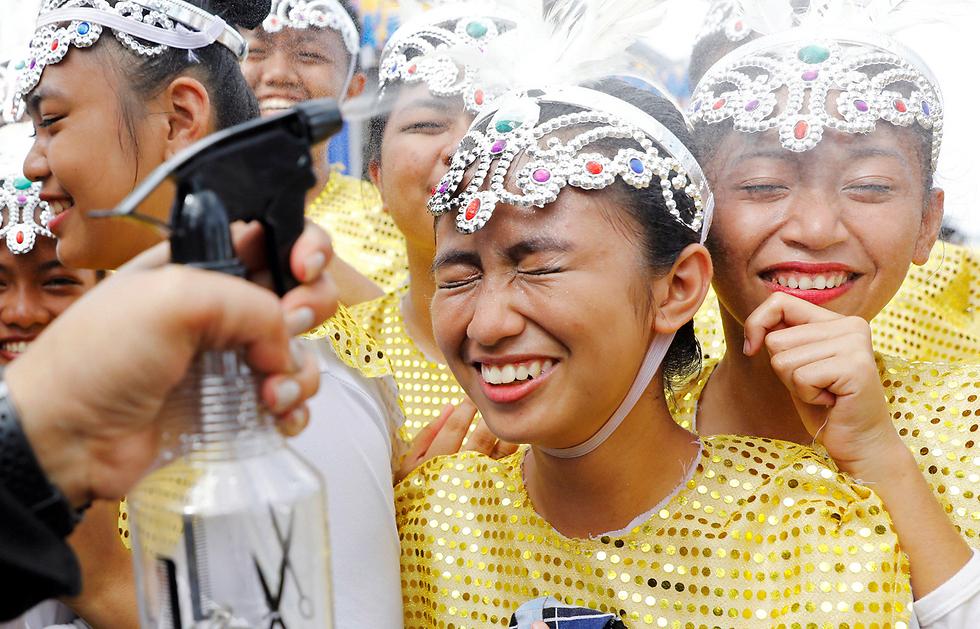 """רקדניות פיליפיניות מתרעננות באמצעות ריסוס מים עליהן לפני הופעתן בטקס קבלת הפנים למנהיגים שמשתתפים בוועדת """"איגוד מדינות דרום-מזרח אסיה"""" (ASEAN) בעיר קלארק שבפיליפינים (צילום: רויטרס) (צילום: רויטרס)"""