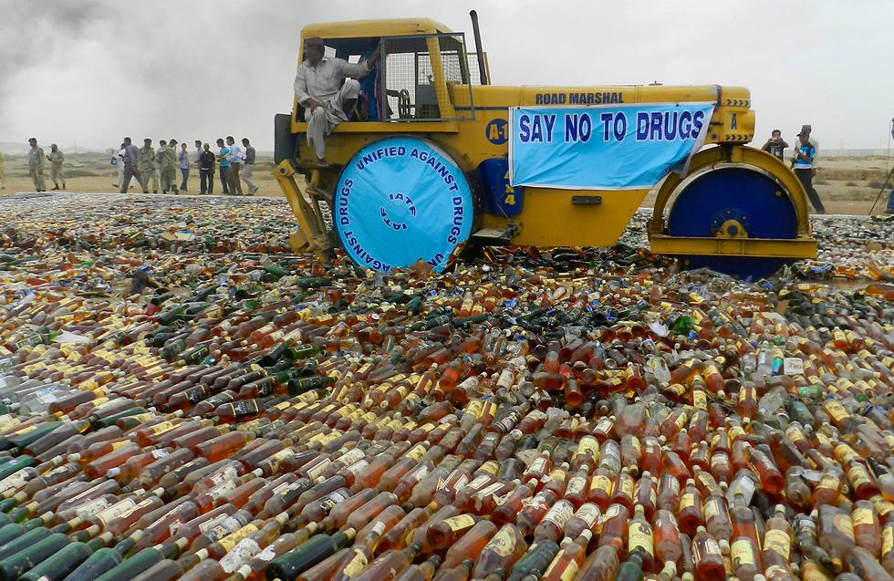 גורמי ממשל פקיסטניים משמידים בקבוקי אלכוהול לא חוקיים שנתפסו בקראצ'י. משמר החופים הפקיסטני השמיד מאות בקבוקי שתייה וסמים שהוברחו לתוך המדינה (צילום: AP) (צילום: AP)