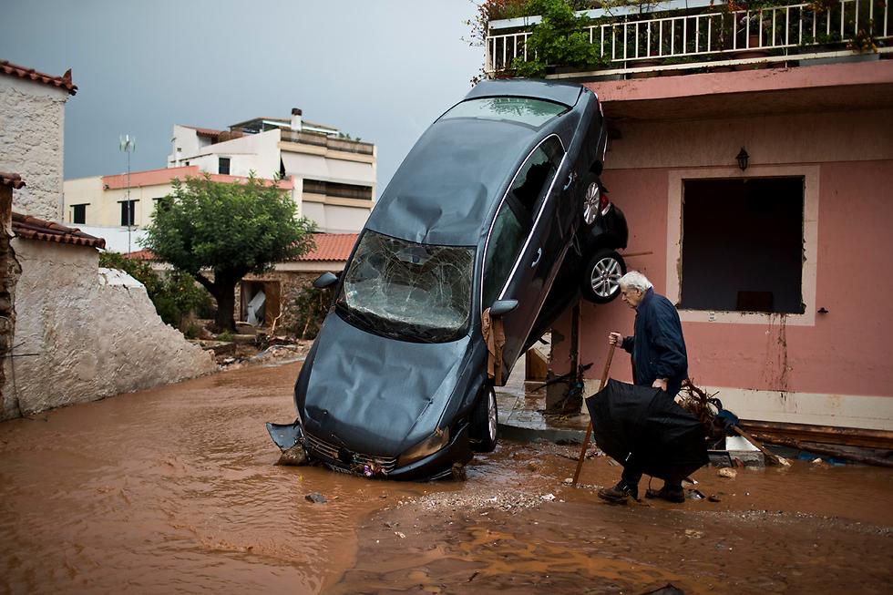 לפחות 14 בני אדם נהרגו בשיטפונות שפקדו את אזור מערב אתונה, יוון. בתצלום: מכונית שעפה על בית בעיר מאנדרה (צילום: AP) (צילום: AP)