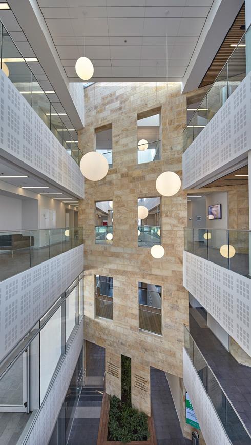 האטריום מתנשא לכל גובה הבניין, והחצר הפנימית מוארת ומאווררת. קיר האבן מהחזית ניכר גם בתוך הבניין   (צילום: ליאור אביטן)