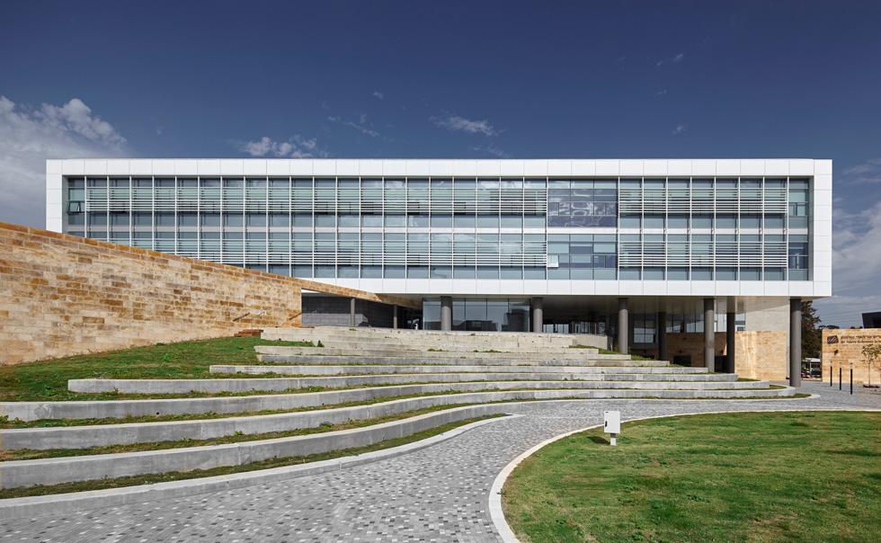 החזית הייצוגית מתנשאת בחלקה על עמודים ומוקפת מסגרת לבנה ומסכי זכוכית . קיר האבן (משמאל) פורץ אל המבנה   (צילום: ליאור אביטן)