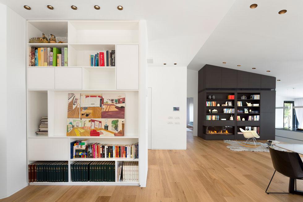 ספרייה לבנה בסטודיו של בעלת הבית, שנבנה במקום המטבח הישן. לצדו פינת אוכל מוגבהת, מופרדת מהסלון במעקה זכוכית (צילום: שי אפשטיין)