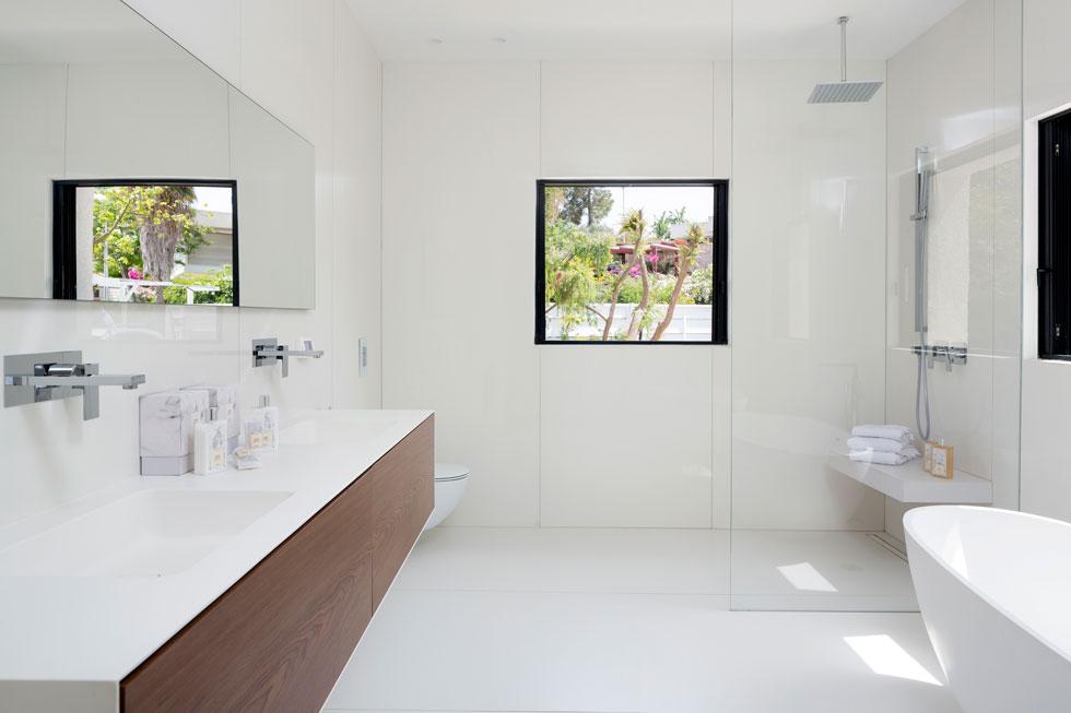 חדר הרחצה לבן כולו, מחופה בפלטות דקיקות של גרניט פורצלן לבן, ואת נגיעת הצבע מספק חיפוי העץ של הארון (צילום: שי אפשטיין)