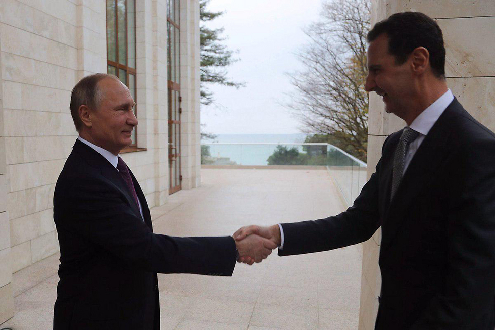 Putin (L) and Assad shake hands in Sochi