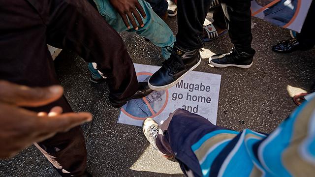 דורכים על תמונת מוגאבה, הערב בבירה (צילום: AP) (צילום: AP)