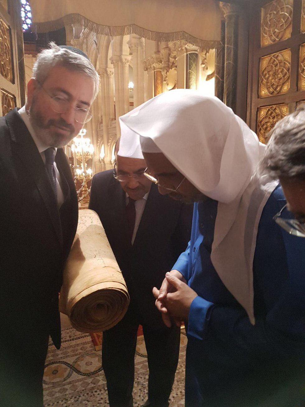 Rabbi Sabag showing the Saudi officials the 200-year-old Torah scroll