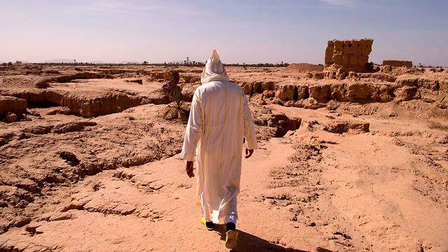 פעם זה היה נווה מדבר: גבר הולך באזור צחיח סמוך לעיר ארפוד (צילום: AFP) (צילום: AFP)