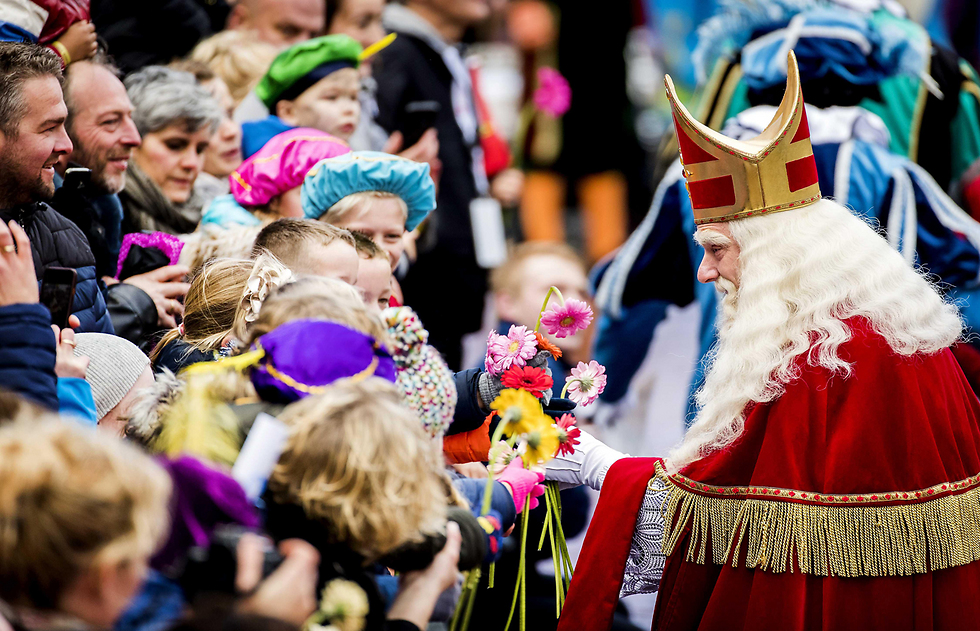 אדם לבוש בבגדי הקדוש ניקולאס (סינטרקלאס) פוגש ילדים בעיר דוקום, הולנד. סינטרקלאס הוא המקור לדמותו של סנטה קלאוס במסורת הצפון אמריקנית (צילום: EPA) (צילום: EPA)