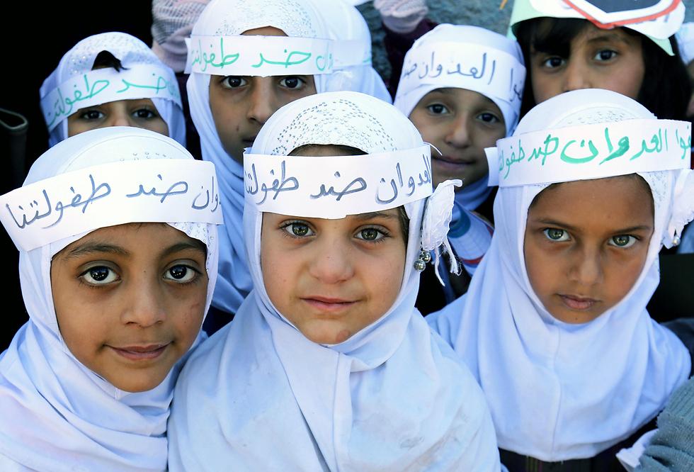 """ילדים מפגינים מחוץ למשרדי האו""""ם בצנעא, בירת תימן, במחאה על מלחמת האזרחים המתמשכת במדינה. """"התוקפנות היא נגד הילדות שלנו"""", נכתב על גבי סרטים שנקשרו סביב ראשיהם (צילום: EPA) (צילום: EPA)"""