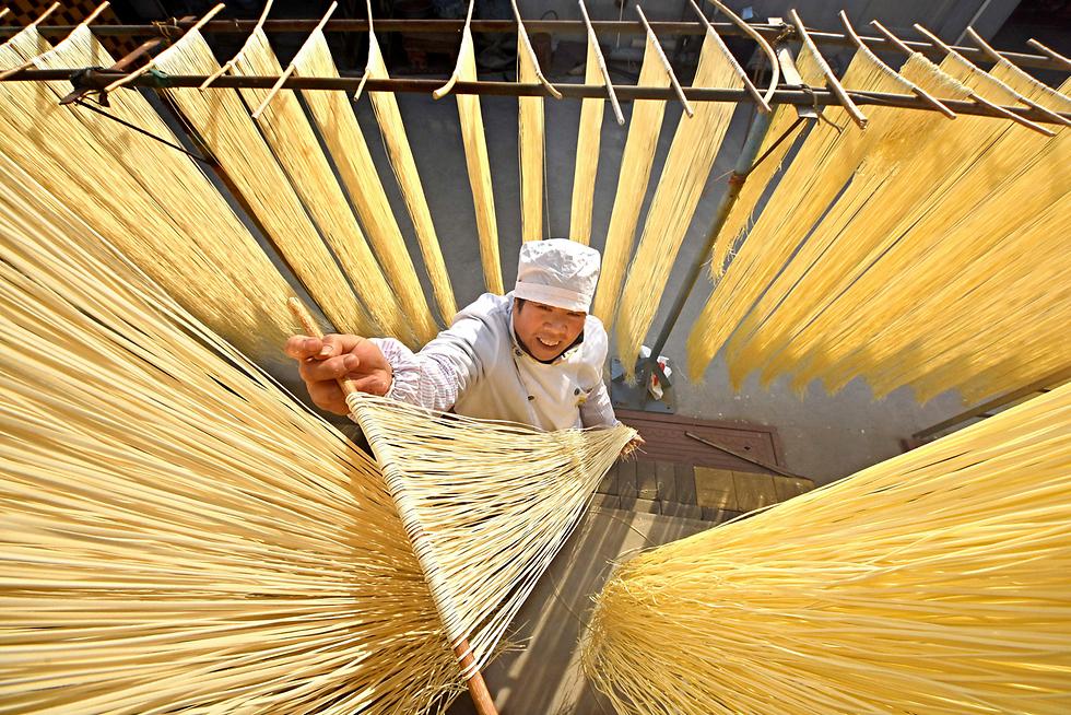 תושב הכפר ליניי בסין תולה נודלס תוצרת בית לייבוש (צילום: רויטרס) (צילום: רויטרס)