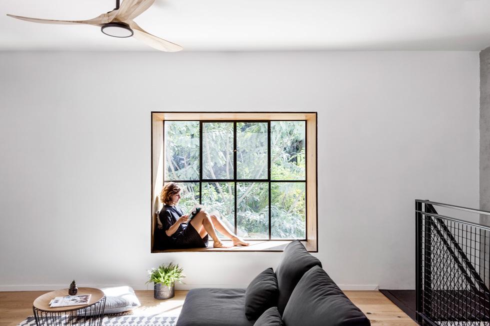 מסגרת החלון בגלריה חופתה בעץ והוא משמש כחלון ישיבה. הנוף הירוק נכנס הביתה  (צילום: איתי בנית)