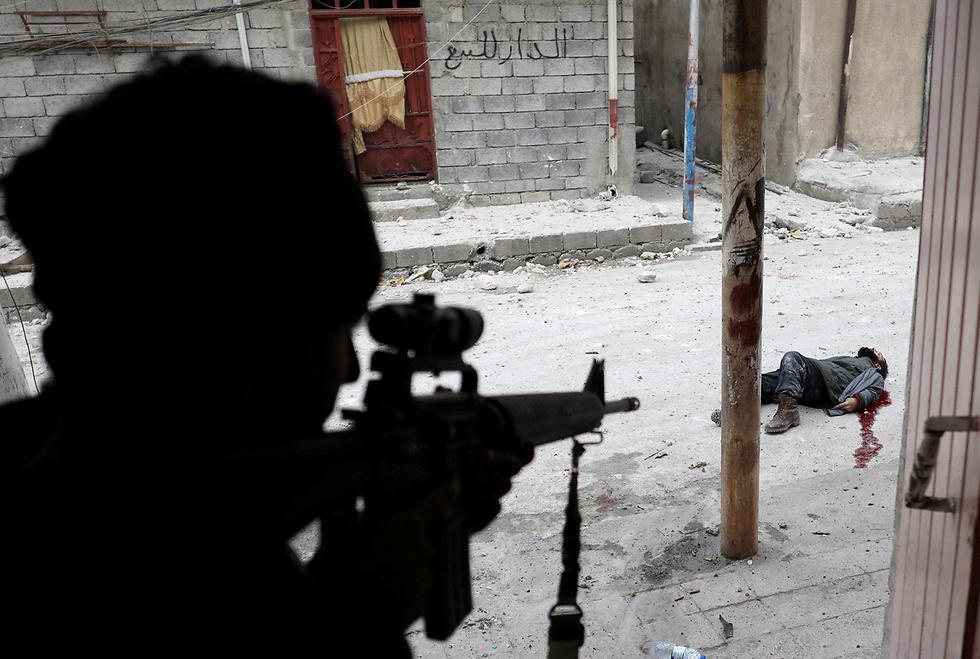 חייל עיראקי יורה במחבל מדאעש (צילום: רויטרס)