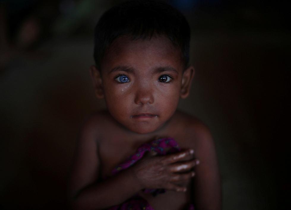 חוסני ארא, פליט בן 4 ממיאנמר, מאזין למקהלת ילדים בבנגלדש, שם מצאה משפחתו מקלט (צילום: רויטרס)
