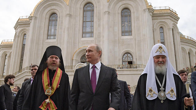 Father Tikhon (L) is considered close to Russian president Putin (center) (Photo: AP)