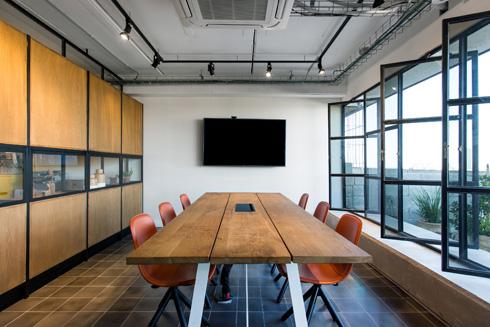 חדר הישיבות מופרד מהמרחב העבודה המשותף. משמאל: מחיצה שמצדה השני משמשת לאחסון ולדקורציה (צילום: שירן כרמל)