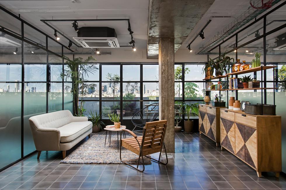 משרדי חברת ''אדיר סחר'' בבניין פנורמה בדרום תל אביב. חלל בן 200 מטרים רבועים, שפונה כולו למרפסת ולנוף. הלובי עוצב כסלון ביתי (צילום: שירן כרמל)