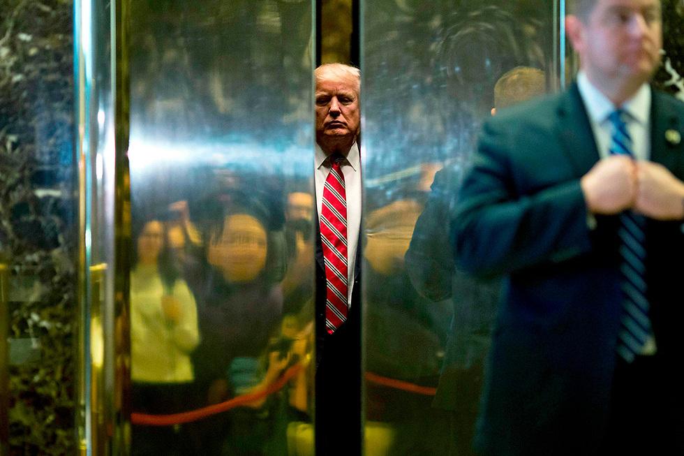 """נשיא ארה""""ב דונלד טראמפ נכנס למעלית במגדל טראמפ בניו יורק, אחרי פגישה עם מרטין לותר קינג השלישי (צילום: AFP)"""