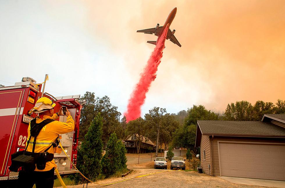 מטוס כיבוי מנסה להשתלט על האש במהלך שריפות ענק בקליפורניה (צילום: AFP)