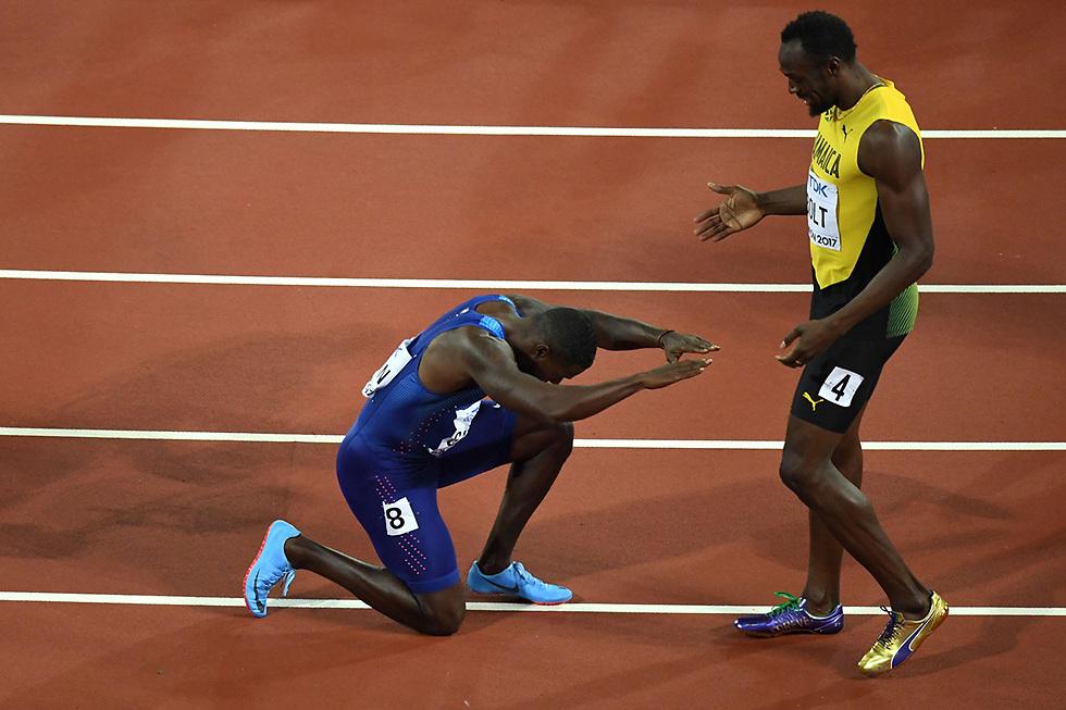 ג'סטין גטלין משתחווה לפני אצן הענק יוסיין בולט, אחרי שניצח את בולט וזכה בזהב בגמר הריצה ל-100 מטר באליפות העולם באתלטיקה (צילום: AFP)