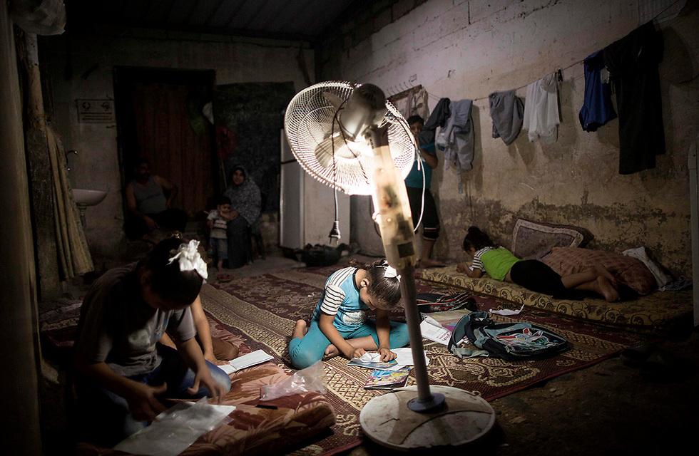 ילדים מכינים שיעורי בית בחום הקיץ של עזה (צילום: AFP)