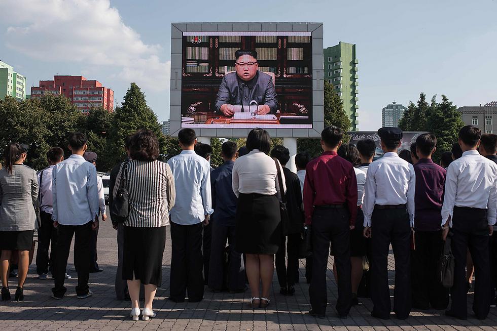 שליט צפון קוריאה קים ג'ונג און נואם, אזרחים צייתנים מקשיבים לו בבירה פיונגיאנג (צילום: AFP)