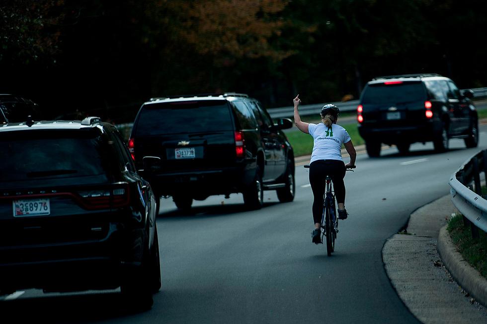 """רוכבת אופניים מסמנת אצבע משולשת לנשיא ארה""""ב דונלד טראמפ בווירג'יניה (צילום: AFP)"""