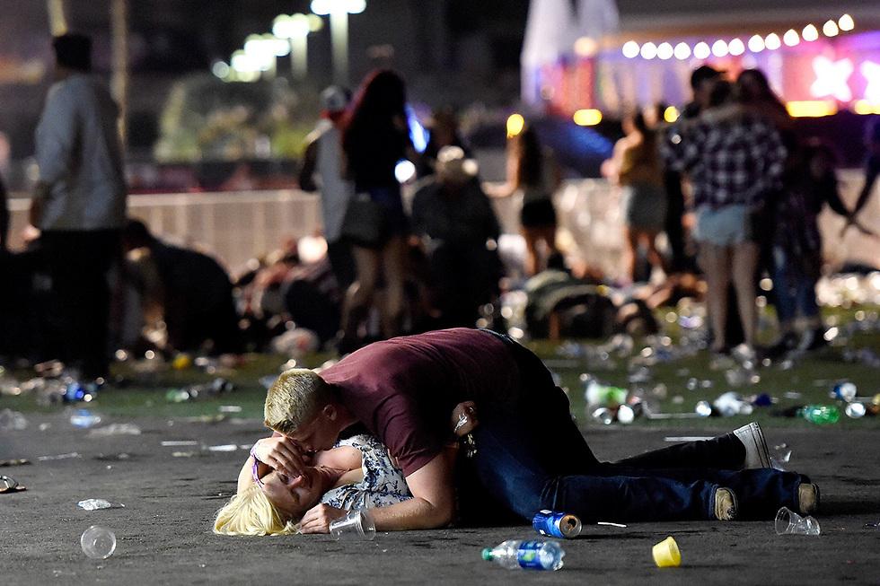 """גבר שוכב על אחת הנפגעות בטבח בלאס וגאס שבו רצח יורה ממלון """"מנדליי ביי"""" 59 בני אדם (צילום: AFP)"""