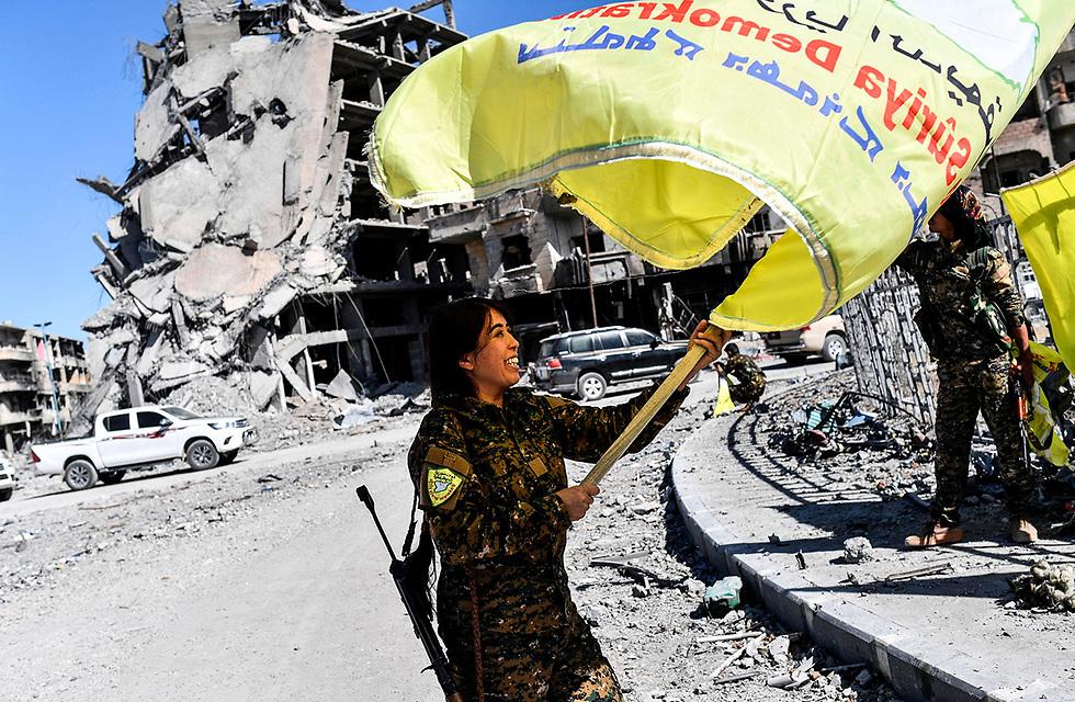 שחרור כיכר א-נעים בעיר ראקה, בירתו של דאעש בסוריה. בתמונה: חיילת מכוחות המורדים הסורים מניפה את דגלם בכיכר, שנודעה ככיכר ההוצאות להורג של ארגון הטרור (צילום: AFP)
