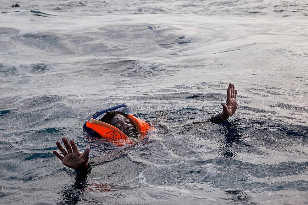מהגר מנסה להגיע לסירת הצלה בגרמניה אחרי שסירתו טבעה. חמישה אנשים שהיו עליה, בהם ילד, טבעו (צילום: AFP)