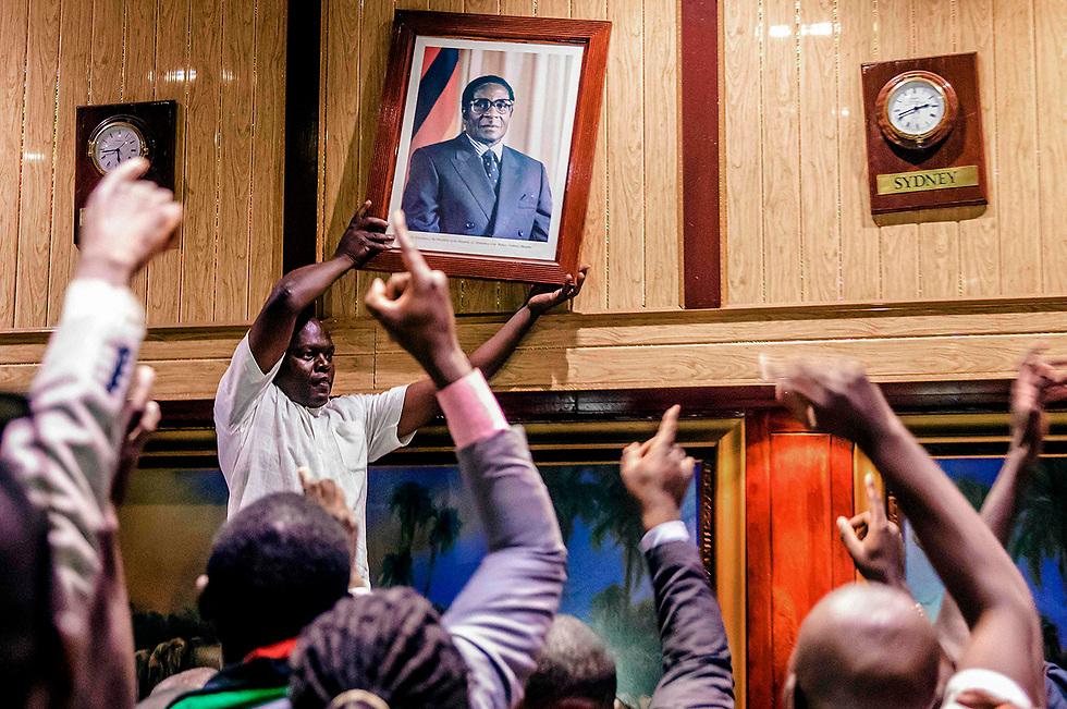 מסירים את תמונתו של שליט זימבבואה רוברט מוגאבה ממרכז הכנסים הבינלאומי בבירה הרארה. שם נערכה הישיבה שבה הודח הרודן אחרי 37 שנה בשלטון (צילום: AFP)