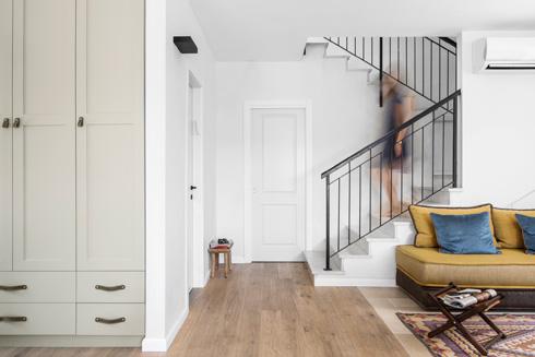 פינת המרבץ צמודה לגרם המדרגות. הדלת הלבנה מובילה לשירותי האורחים   (צילום: איתי בנית)
