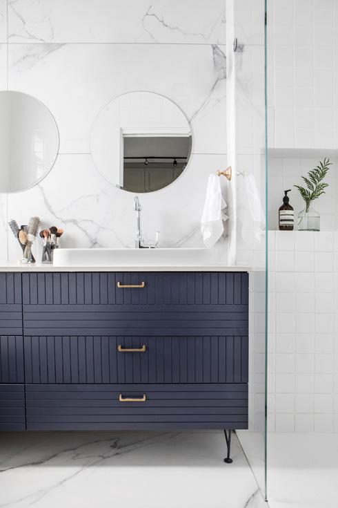 ארון הכיור כחול עם ידיות פליז. הקיר מחופה באריחים דמויי שיש קררה  (צילום: איתי בנית)