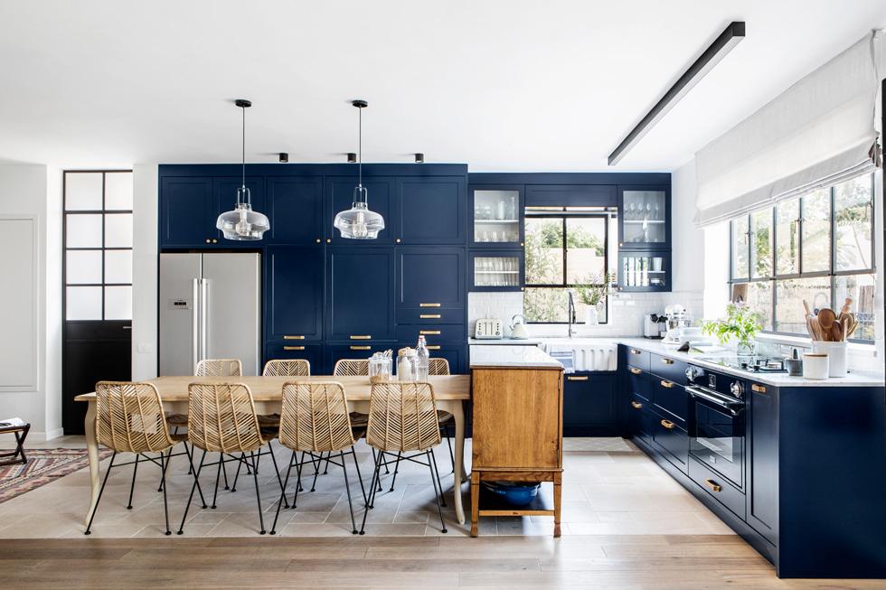 המטבח הוא העוגן העיצובי של הקומה, לא רק בשל גודלו ופתיחותו אלא בעיקר בזכות הגוון הכחול שבו הוא צבוע. הוא יוחד גם באמצעות רצפת האבן (צילום: איתי בנית)