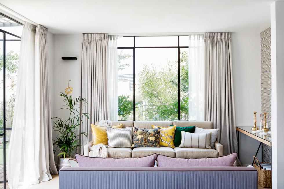 """""""המטרה של פתיחת החלון הגדול שמעל הספה בסלון היתה ליצור גלויה ירוקה"""", מסבירה גרוס, והחדר משופע בטקסטיל - מטפט ועד כריות (צילום: איתי בנית)"""