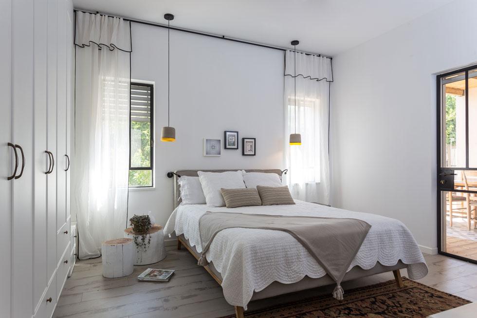 """המיטה בחדר ההורים ממוקמת בין שני חלונות. מהחדר יש יציאה לפינת אוכל חיצונית. """"חדר השינה"""", אומרת אבן הר, """"הוא הסלון הפרטי שלנו""""  (צילום: לימור הרצוג אהרוני)"""