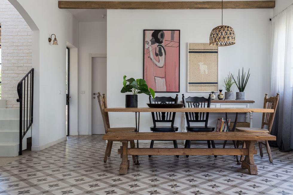 """שולחן האוכל הוא """"מרכז העניינים"""". מאחוריו שידה קטנה ומעליה עבודות אמנות. העבודה מימין: הדפס של דנה ניצני. העבודה משמאל: ציור של אבנר בן גל  (צילום: לימור הרצוג אהרוני)"""