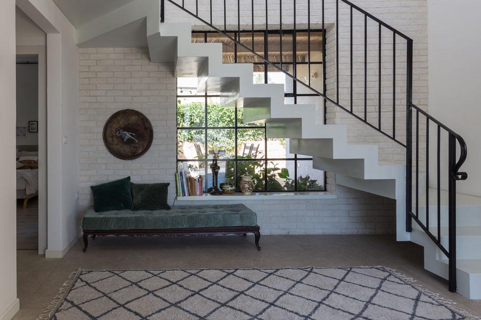 דלת הכניסה נפתחת מול גרם מדרגות וחלון גדול, מחולק בגריד ברזל לריבועים ועטוף בלבנים, שמכניס פנימה אור רב (צילום: לימור הרצוג אהרוני)
