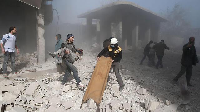אדם מפנה גופת ילד בעיר חמורייה (צילום: AFP) (צילום: AFP)