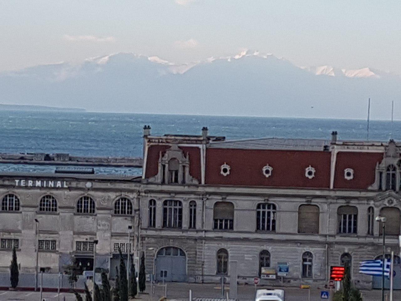 """מביט מכל פינה: הר האולימפוס מול נמל סלוניקי (צילום: אחיה ראב""""ד)"""